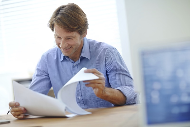Shot of a smiling businessman looking over some paperwork while sitting at his desk